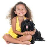 拥抱她的爱犬的逗人喜爱的小女孩 免版税图库摄影