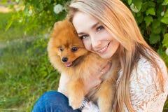 拥抱她的爱犬红色波美丝毛狗的愉快的美丽的柔和的女孩 库存照片