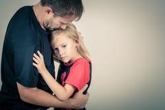拥抱她的父亲的一个哀伤的女儿画象  免版税库存照片
