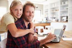 拥抱她的父亲的女孩,在家研究膝上型计算机 免版税库存图片