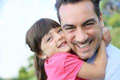 拥抱她的父亲的小女孩画象 免版税图库摄影