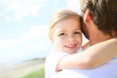 拥抱她的父亲的小女孩 库存图片