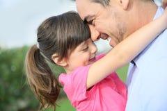 拥抱她的父亲的小女孩 免版税库存图片