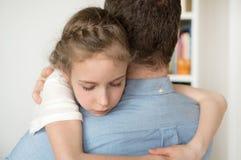 拥抱她的爸爸的女孩 免版税库存照片