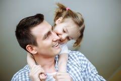 拥抱她的爸爸的小女孩画象 浅深度的域 免版税库存照片
