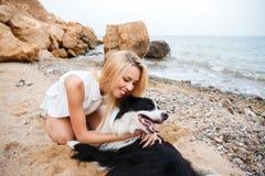 拥抱她的狗和微笑在海滩的愉快的妇女 库存照片