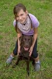 拥抱她的狗朋友的小女孩 免版税库存照片