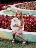 拥抱她的狗的一个女孩的美丽的画象 与一条狗的一个孩子在公园背景 逗人喜爱的家庭宠物 生活概念 库存图片