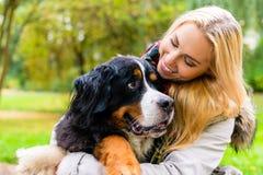 拥抱她的狗的妇女在秋天公园 免版税库存照片