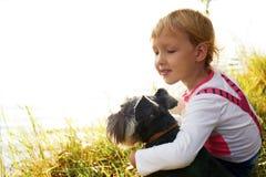 拥抱她的狗的小女孩小女孩 他们看湖 免版税库存照片