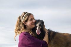 拥抱她的狗的少妇 免版税库存图片