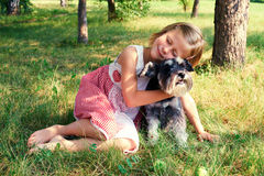 拥抱她的狗的逗人喜爱的女孩 免版税库存图片