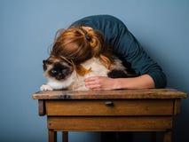 拥抱她的猫的少妇 免版税图库摄影