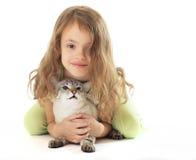拥抱她的猫的美丽的小女孩。 库存照片