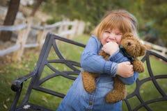 拥抱她的玩具熊的逗人喜爱的微笑的女孩外面 库存照片