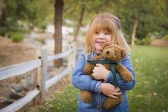 拥抱她的玩具熊的逗人喜爱的微笑的女孩外面 免版税库存照片