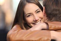 拥抱她的男朋友和看照相机的愉快的女朋友 免版税库存图片