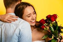 拥抱她的男朋友的愉快的妇女在得到玫瑰花束以后  免版税图库摄影