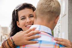 拥抱她的男朋友的美丽的光芒四射的妇女 免版税图库摄影