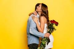 拥抱她的男朋友的美丽的妇女在得到玫瑰花束以后  免版税库存照片