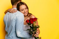 拥抱她的男朋友的高兴的妇女在得到玫瑰花束以后  免版税库存照片