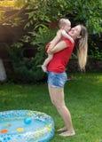 拥抱她的男婴的快乐的母亲在游泳在水池以后 免版税库存图片