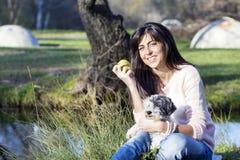 拥抱她的白色狗用苹果的微笑的深色的妇女在手上 免版税库存图片