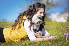 拥抱她的白色狗的少妇室外 图库摄影