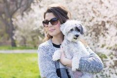 拥抱她的白色狮子狗的美丽的妇女在春天庭院里 库存照片