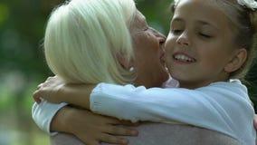 拥抱她的祖母和亲吻在面颊、家庭关心和爱的女孩 影视素材