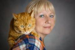 拥抱她的红色猫的妇女 免版税库存图片