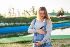 拥抱她的胃的孕妇户外 库存照片