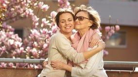 拥抱她的阳台的成人女儿母亲反对一株开花的木兰的背景 妇女在灰棕色打扮 股票视频