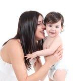 拥抱她的婴孩的可爱的母亲 免版税库存照片