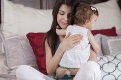拥抱她的婴孩的愉快的母亲 免版税库存照片