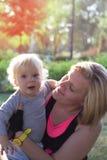 拥抱她的婴孩的母亲在公园 免版税库存照片