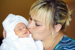 拥抱她的婴孩的爱恋的母亲 免版税库存照片