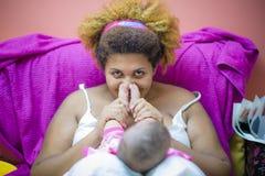 拥抱她的婴孩脚的非裔美国人的母亲 免版税库存照片