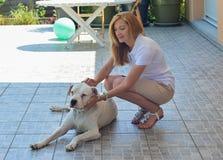 拥抱她的dogo argentino的白肤金发的女孩 免版税库存图片