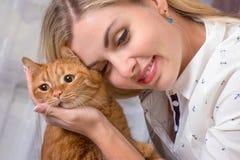 拥抱她美丽的红头发人猫的年轻女人 对动物的爱 免版税图库摄影