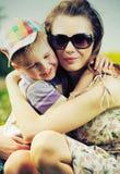 拥抱她逗人喜爱的儿子的美丽的妈妈 免版税库存图片