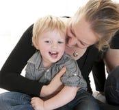 拥抱她逗人喜爱的白肤金发的小孩的年轻母亲 免版税库存照片