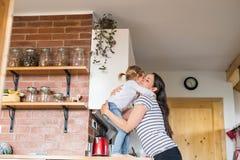 拥抱她逗人喜爱的矮小的女儿的美丽的年轻母亲 免版税库存照片