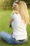 拥抱她逗人喜爱的约克夏狗的年轻白肤金发的妇女 图库摄影