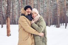拥抱妇女的愉快的白种人人在一个冷漠的森林里 库存照片