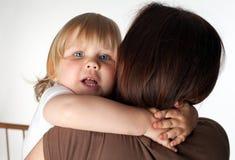拥抱妈咪哀伤的小的年轻人的女孩 免版税库存照片