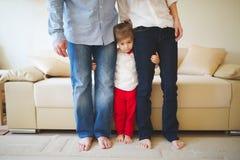 拥抱妈妈和爸爸腿的女孩 库存照片