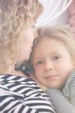 拥抱妈妈的女儿 库存照片