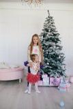 拥抱妹的女孩在圣诞树和礼物盒附近 免版税库存图片