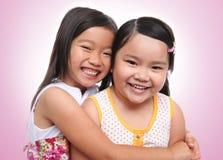 拥抱姐妹的亚洲人二个年轻人 库存图片